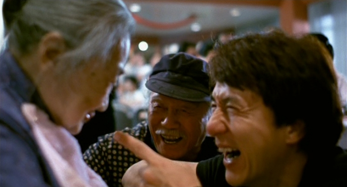 """Fig. 4: During a party, Papa Chan tells a funny family story that makes Jackie and his sick mother laugh, around 2002. (Source: """"Traces Of A Dragon"""" DVD, Universum Film)"""
