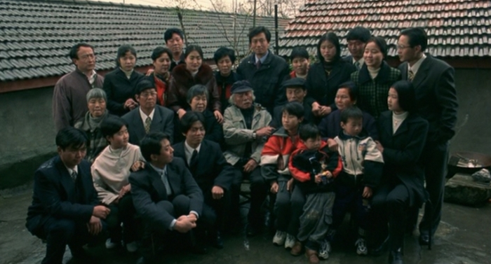 """Fig. 5: Jackie Chan's father Charles Chan Chi-Ping visits his home town of Wuhu as the head of the family and meets his extended family around 2002. On his right side sits the older daughter of his wife Lily Chan, Chan Yulan, Jackie's half-sister. (Source: """"Traces Of A Dragon"""" DVD, Universum Film)"""